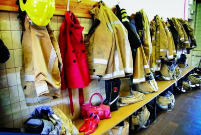 Photo of empty locker room with woman's coat among firefighter kit