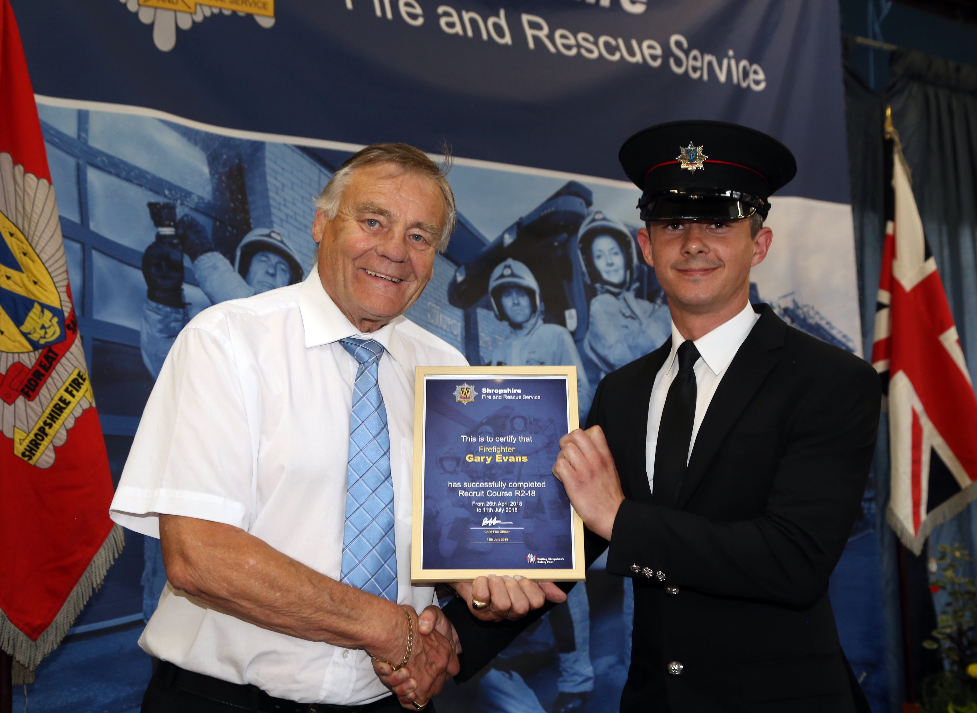 Shropshire and Wrekin Fire Authority chairman, Councillor Eric Carter, presents recruitment certificates to firefighters. Gary Evans also won the instructors' award