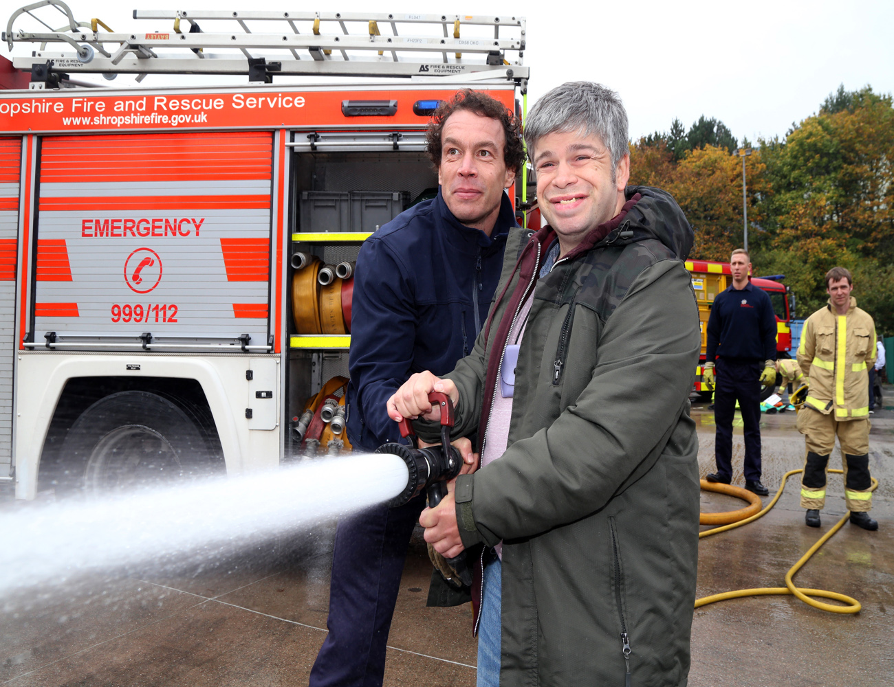 Firefighter Martin Poole shows Martin McCusker how to put out fires.