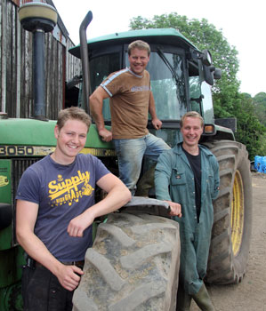 Three brothers pictured on the farm with a tractor