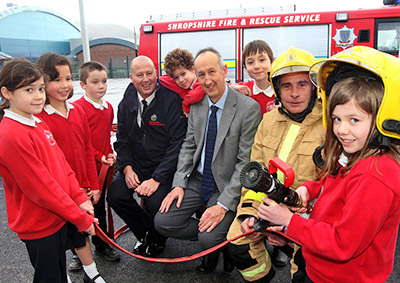 A posed group shot of 6 kids, headteacher, and 2 firefighters in front of fire appliance
