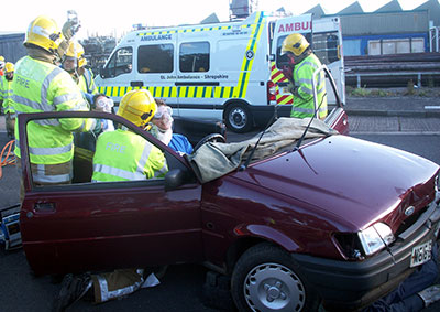 Photo of firefighters extracting a lady from the wreckage of a car with an ambulance in the background