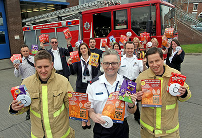 A group of fire service staff hold leaflets and smoke alarms towards the camera standing outside next to fire engine