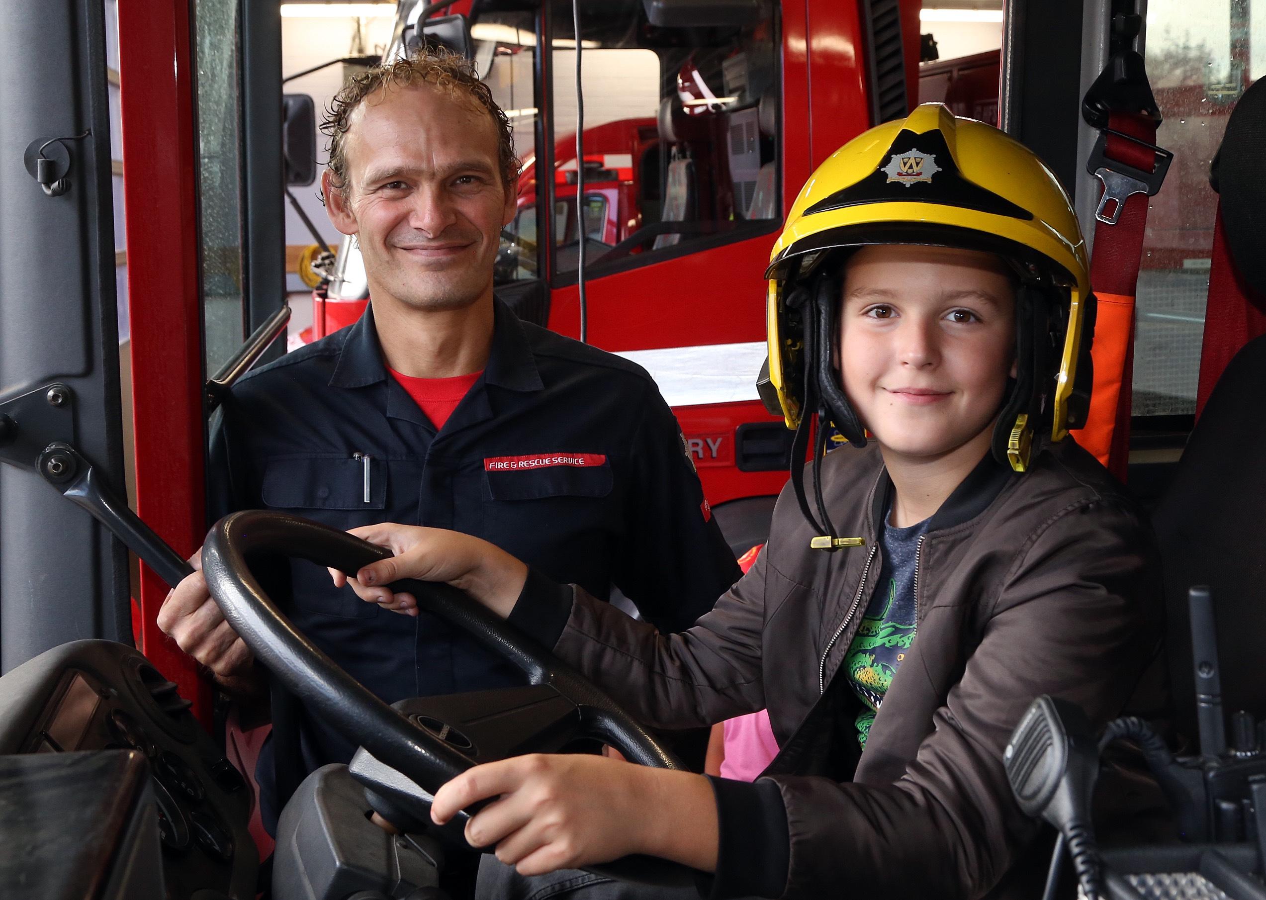 Aboard a fire engine with firefighter  Jon Robinson is Zhenya Shatilo (age 12).