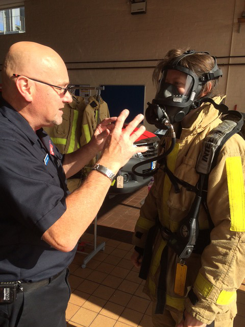 Firefighter Shaun Powell shows Becca Peace-Winn how the breathing apparatus works.