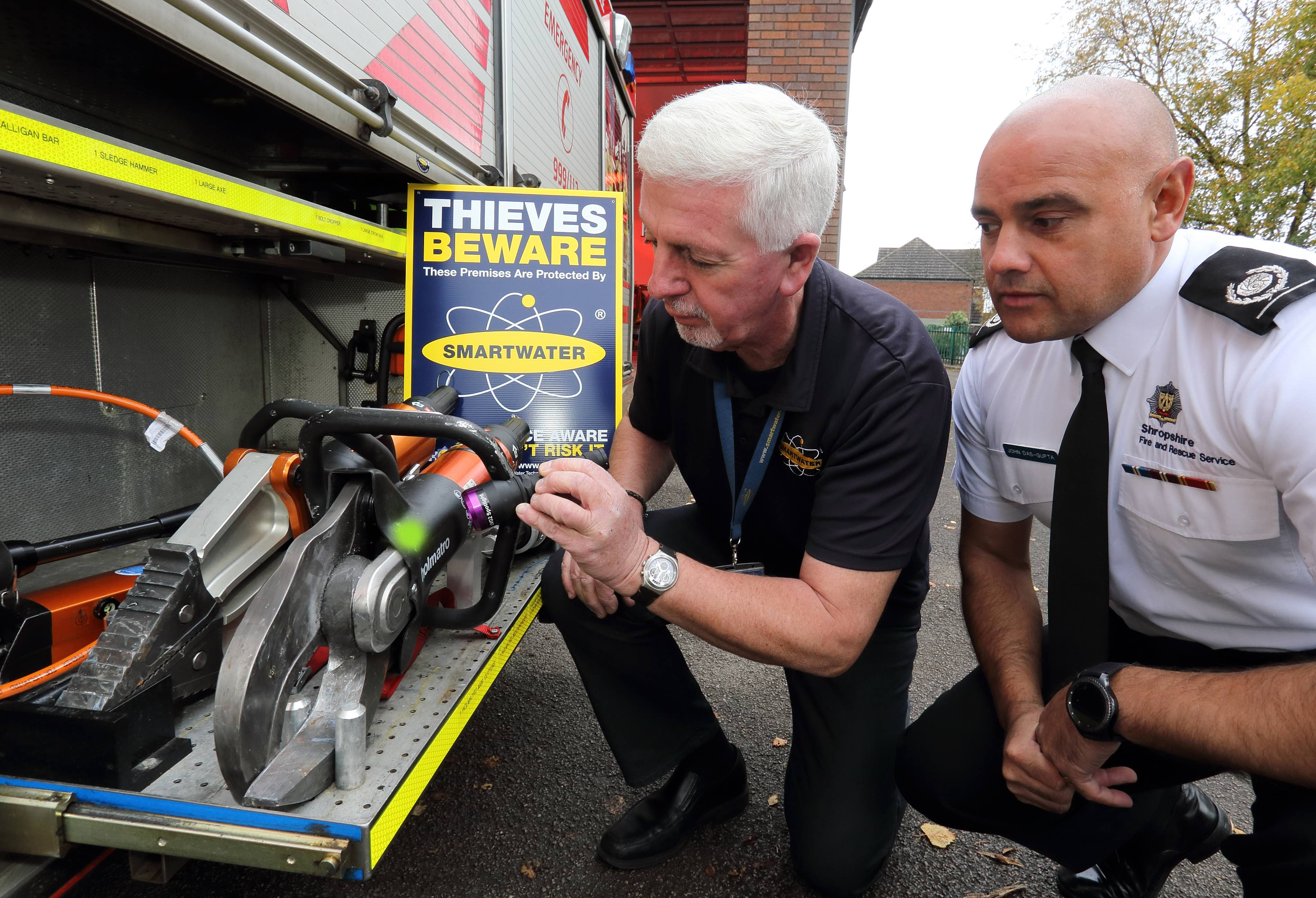 "SmartWater's Steve Mills, a former crime squad officer, shines an ultra violet light to identify stolen equipment and entrap thieves with Area Manager John Das Gupta and Andy Bevon (left), of Shropshire Fire and Rescue Service, at the scene of a ""first ever"" crime at Albrighton Fire Station."