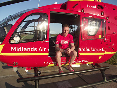 Tim in running gear sitting on the edge of the air ambulance helicopter door on a sunny day