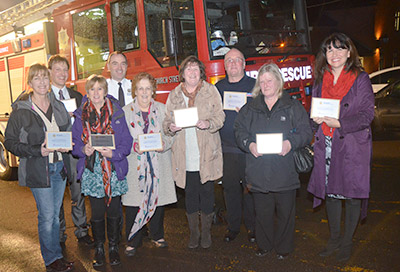 Group shot of employers holding plaques on a dark night in front of a fire appliance