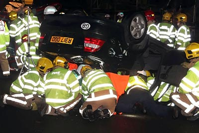 Firefighters attempting to rescue occupants from a car on it's roof