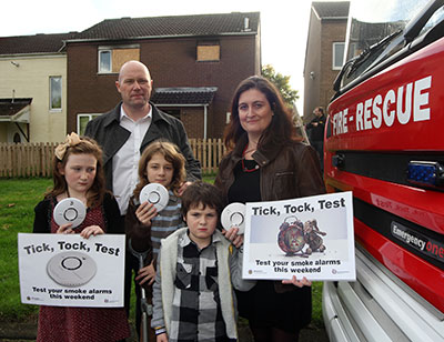 The Fitzsimmons family pictured next to fire appliance holding smoke alarms and 'Tick,Tock,Test' posters