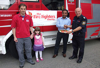Three men and a young girl pictured in front of a fire appliance with a Firefighters Charity banner