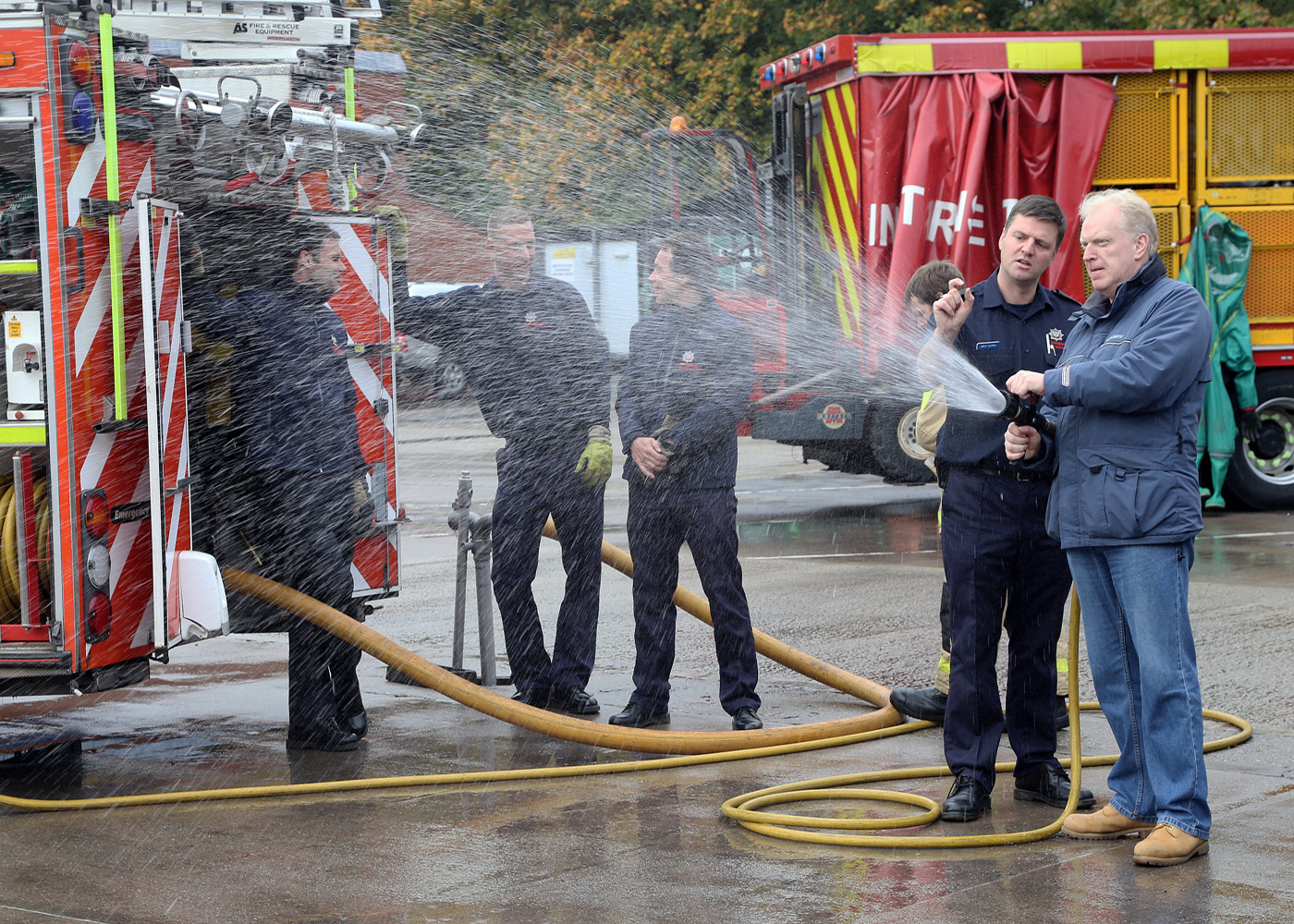 Crew Manager Simon Morris shows a visitor how to operate a fire hose.