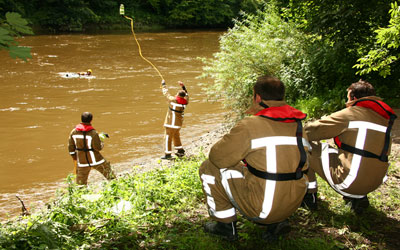 Photo showing a firefighter throwing a float and line out into a river where firefighters are treading water