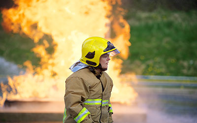 A female firefighter is pictured in protective kit in front of a wall of flames