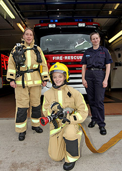 A firefighter in uniform and two taster session women in protective equipment pose to camera
