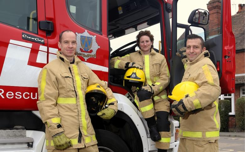 Firefighters pose next to fire engine