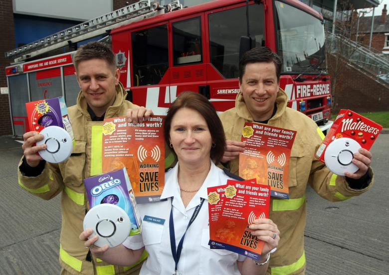 Three fire service personnel holding leaflets and smoke alarms in front of fire engine