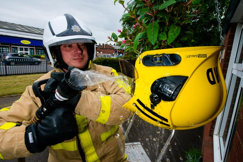 Watch Manager Mark Smith with the recycled helmet used as a flower basket outside Market Drayton fire station in Shropshire. Image courtesy Shropshire Star