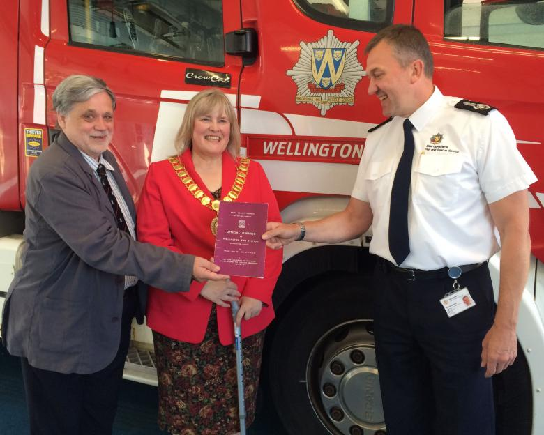 Professor Howard Davies, of the national Fire Brigade Society, with Wellington Mayor Cindy Mason-Morris, presents the original 1953 opening programme to Chief Fire Officer Rod Hammerton.
