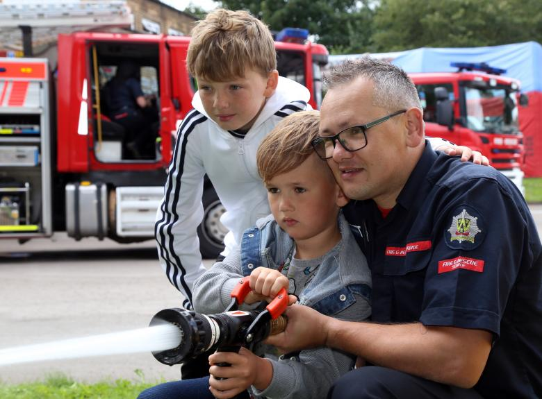 On Call firefighter Steve Breese shows Ethan and Matthew Breese how to use the fire hose at Wellington Fire Station's annual open day.
