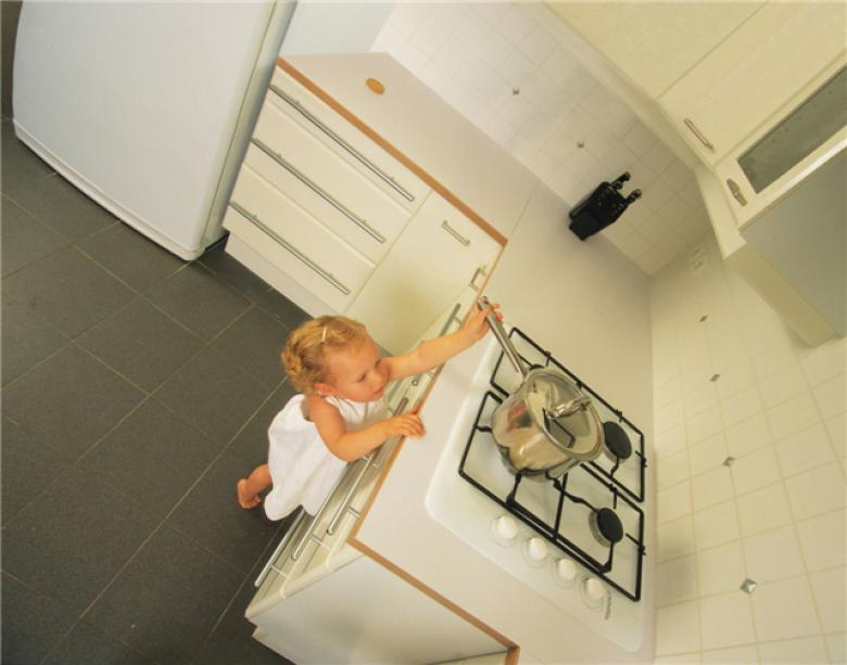 Girl stretches to reach cooker hob