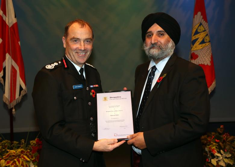 Rabinder Dhami receives his award from Chief Fire Officer John Redmond