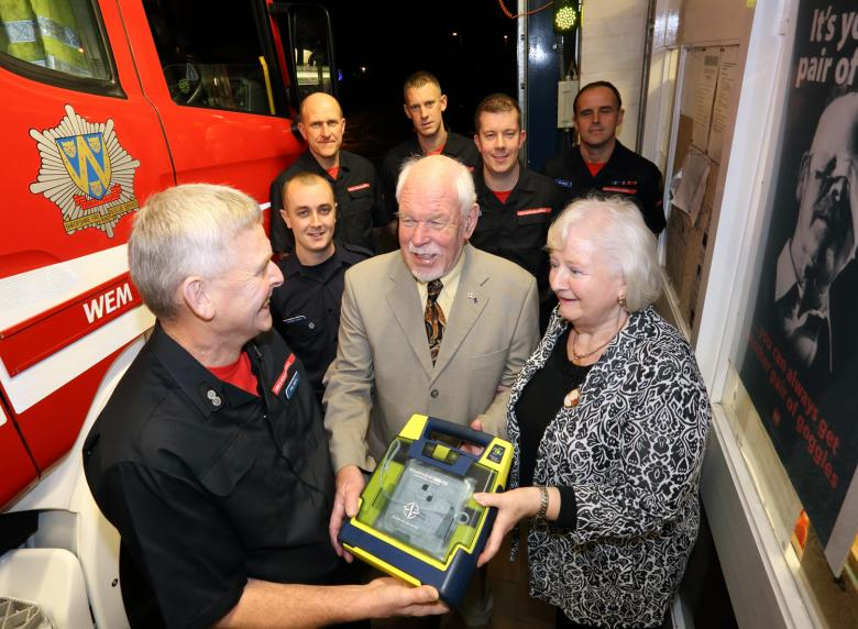 Pensioner John Luce and wife Margaret say thank you to Wem firefighters' for saving his life. Pictured are Watch Manager Phil Smith (front) with the defibrillator used to carry out the lifesaving rescue with back row, L-R, Darren Jones, Jon Green, Gary France, Leon Turner and Vic Young.