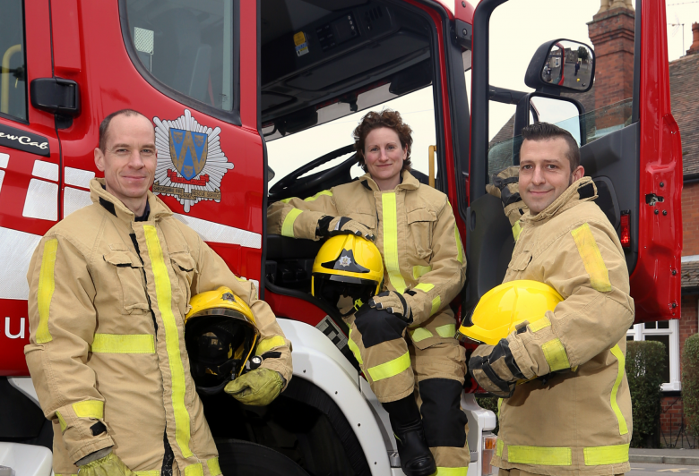 Three firefighters pose with a fire appliance